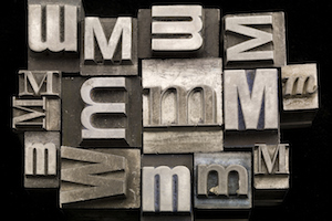 random letter M letterpress on black background